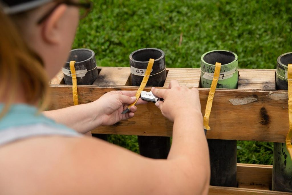Jill Compogno uses a box cutter to set up a row of fireworks in Spokane's Riverfront Park on Tuesday, July 3, 2018. Compogno has volunteered with Pyro Spectaculars, the company in charge of the fireworks show, for seven years. (Libby Kamrowski / The Spokesman-Review)