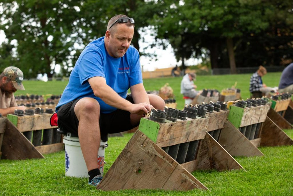 Brian Schmidt, a second-year volunteer with Pyro Spectaculars, helps set up rows of shells in Riverfront Park on Tuesday, July 3, 2018, for the Fourth of July fireworks show. (Libby Kamrowski / The Spokesman-Review)