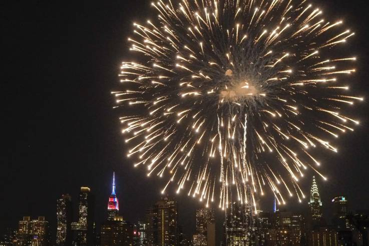The Empire State Building is lit in blue, white and red as people watch the Macy's Fourth of July Fireworks from Hunter Point Park on July 4, 2018 in New York City. EDUARDO MUNOZ ALVAREZ/GETTY