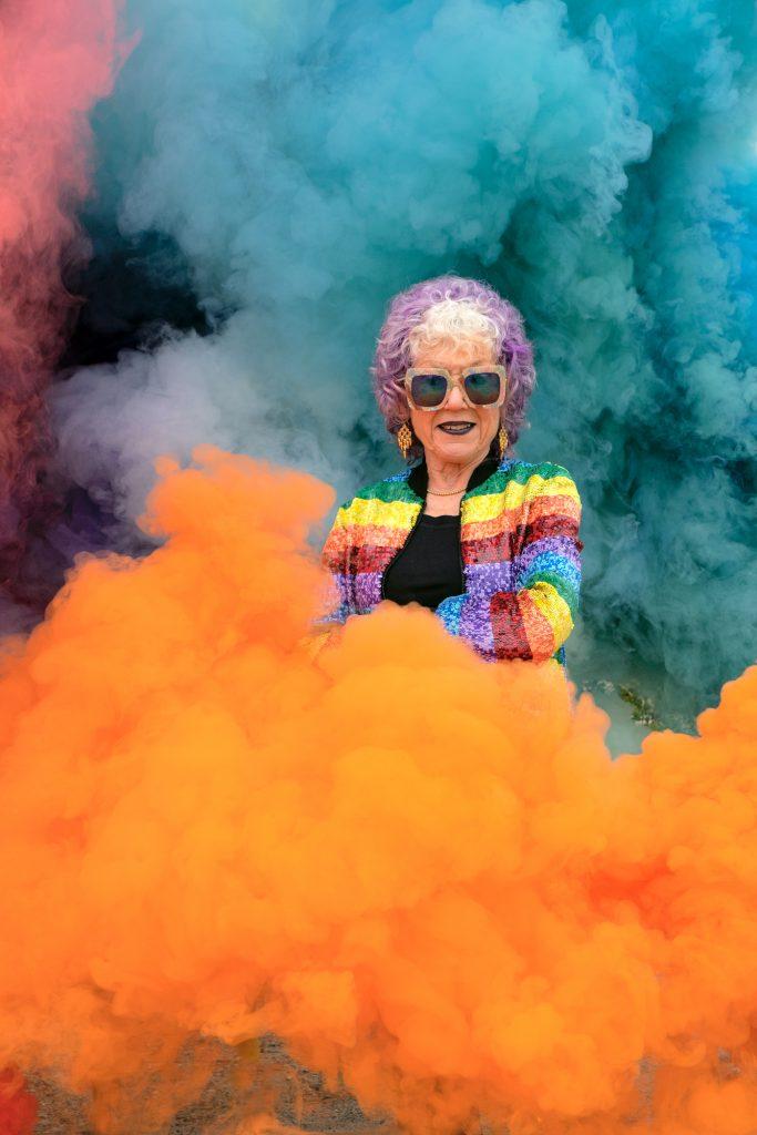Judy Chicago stands in her rainbow smoke art