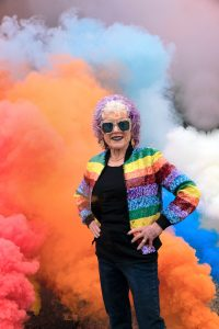 Judy Chicago Stands in her rainbow smoke art